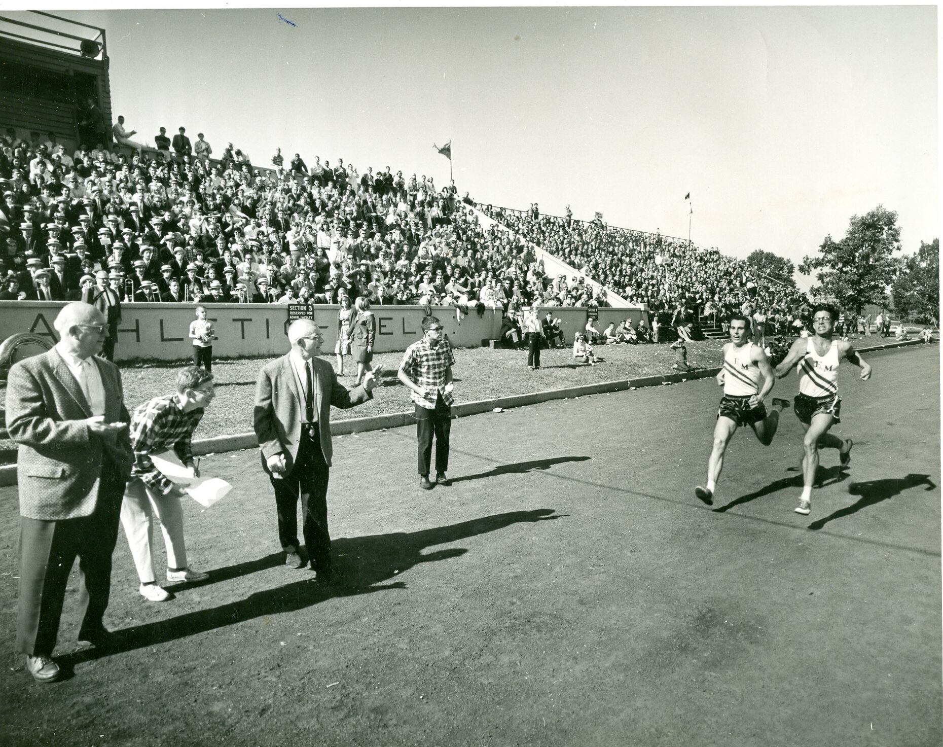 Runners John Buddington and Dave Thome finish a race at Williamson Field.