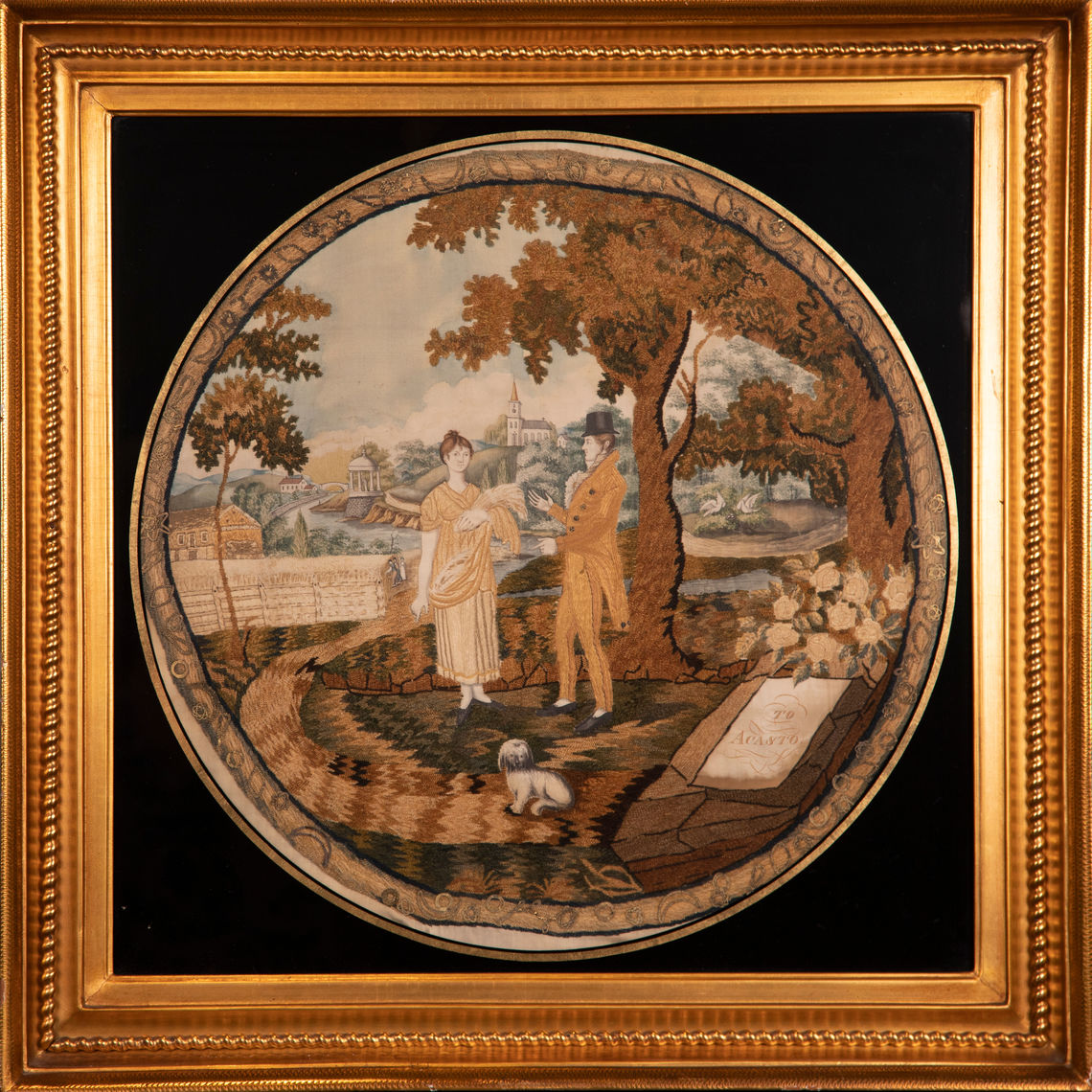 "The circular needlework embroidery shows a young woman holding stalks of grain in her left arm talking to a well-dressed young man near a large tree. A white dog sits in the foreground along with a memorial ""TO ACASTO,"" an ancient Greek king. A river in the background separates the foreground fields from the town background, which includes a church, a classical temple, two birds tending a nest, and other images. A narrow border with metallic spangles sewn in place surrounds the composition."