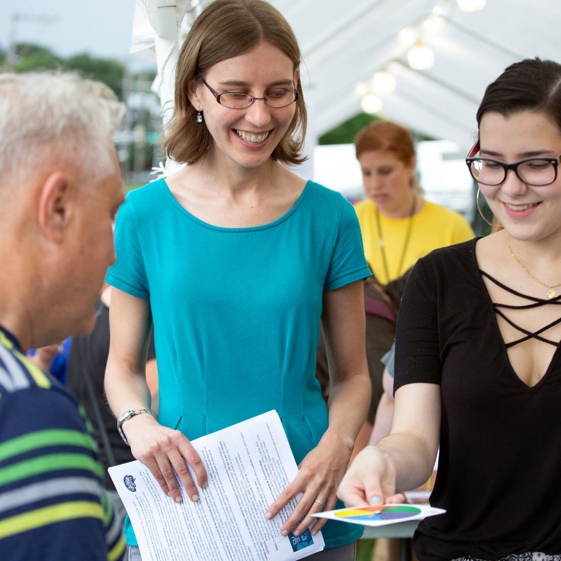 Assistant Professor of Spanish and Linguistics Jessica Cox and sophomore Lilian Rodriguez talk with an attendee of the 35th annual San Juan Bautista Hispanic Festival.