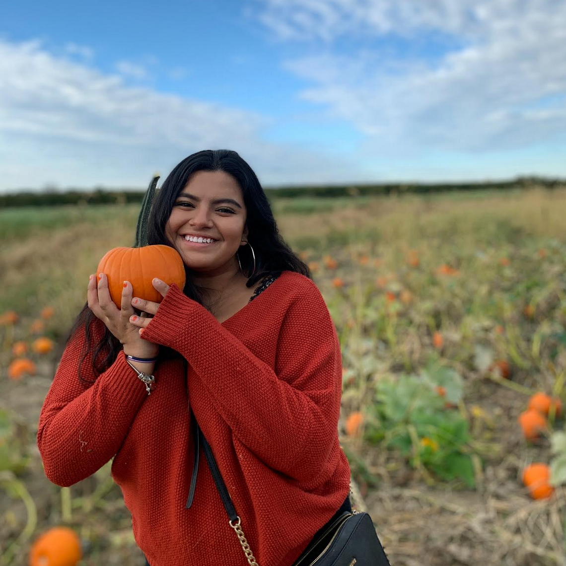 Sheryl smiles at the camera, in an outdoor space holding a small pumpkin.