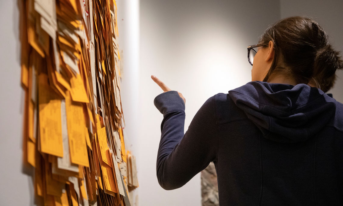 """Visitor pointing to the site-specific installation """"Hostile Terrain 94"""" at the opening reception for """"Hostile Terrain."""" Photo by Deb Grove."""