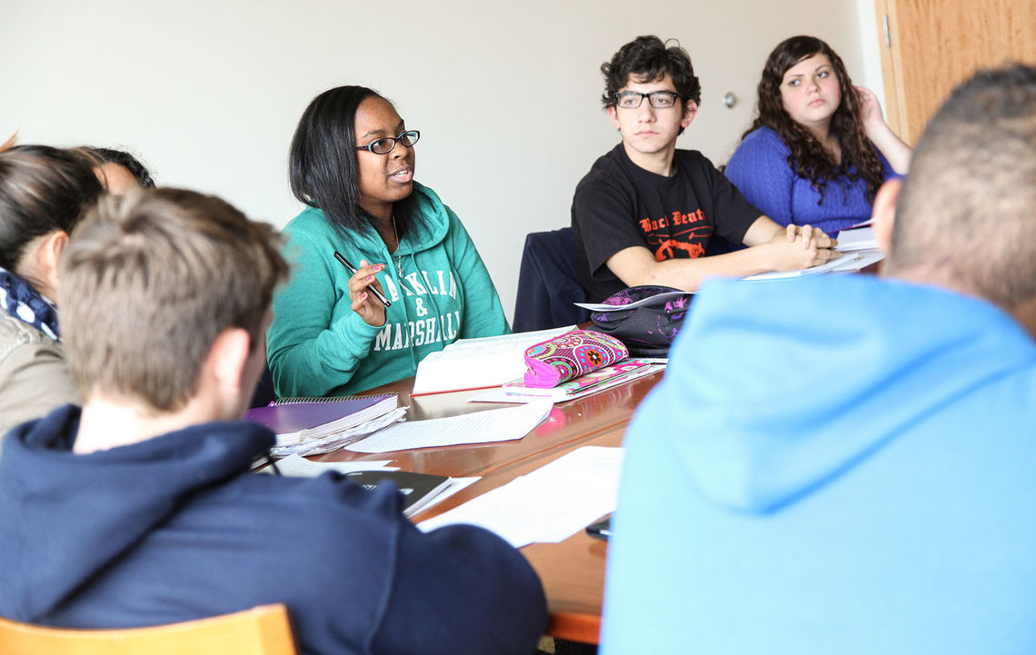 Students attend an English class in a seminar room in Brooks College House with professor Justin Hopkins