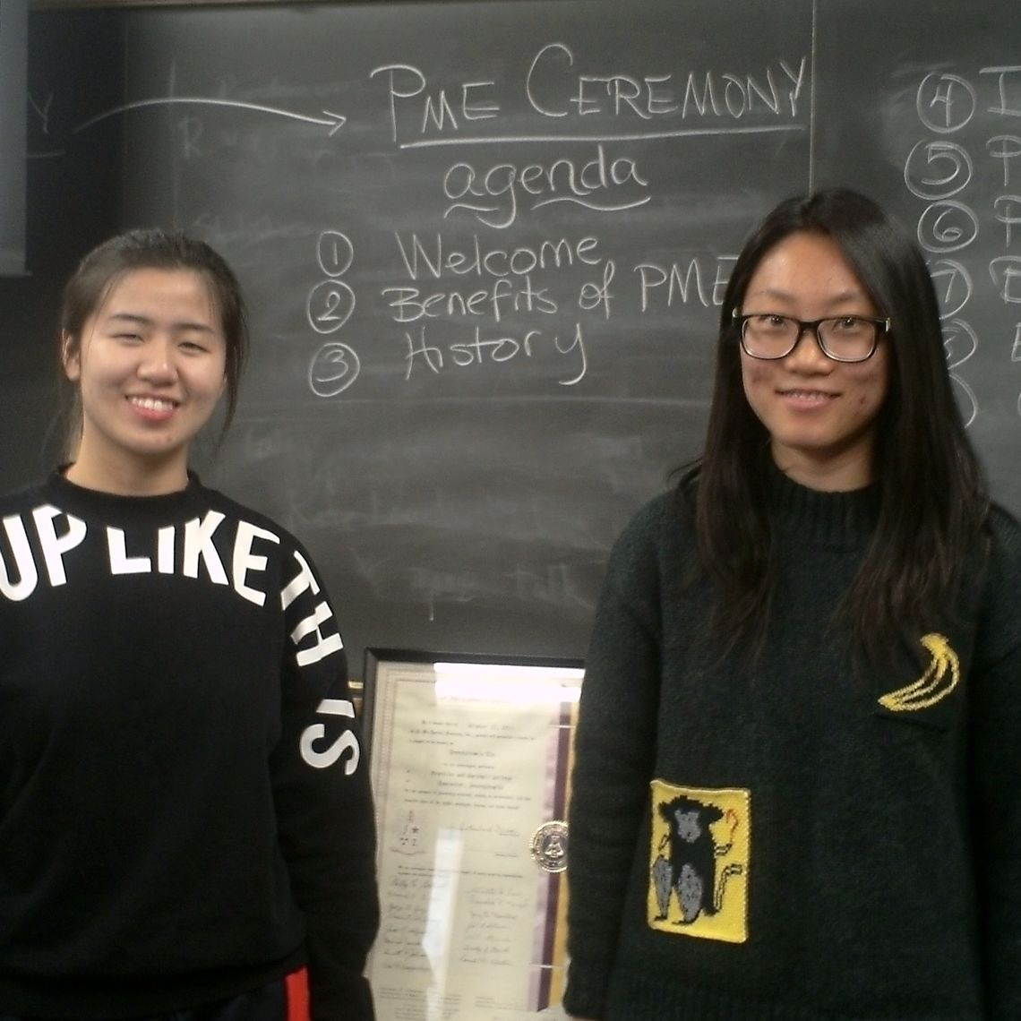 Yinxi Li '19, new Pi Mu Epsilon President for 2018-19, and outgoing President Chengcheng Zhai '18 stand beside the chapter's original charter that dates back to 1963.