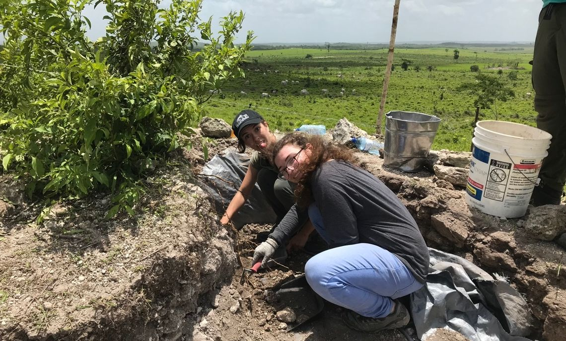 Marissa (in black shirt) excavates a small Maya village on the Belize plains.