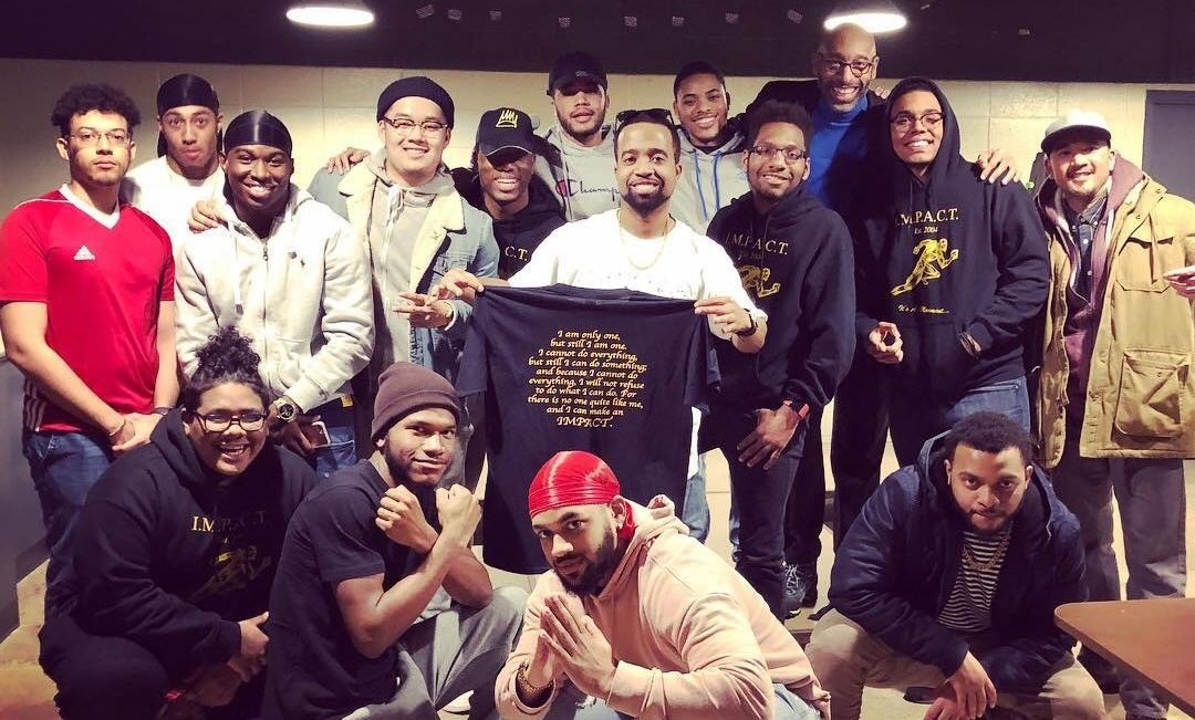 """Hip-hop artist Steve Tyson '07 (center, holding shirt) returned to F&M to perform a concert on March 23, 2018. He is pictured with current members of I.M.P.A.C.T., a student group he founded, as well as Dean Donnell Butler (back row at right, in blue shirt) and AMS Prof. Mark Redondo Villegas (far right, in tan jacket). Prof. Villegas teaches a course called """"Hip Hop: Global Politics and Culture."""""""