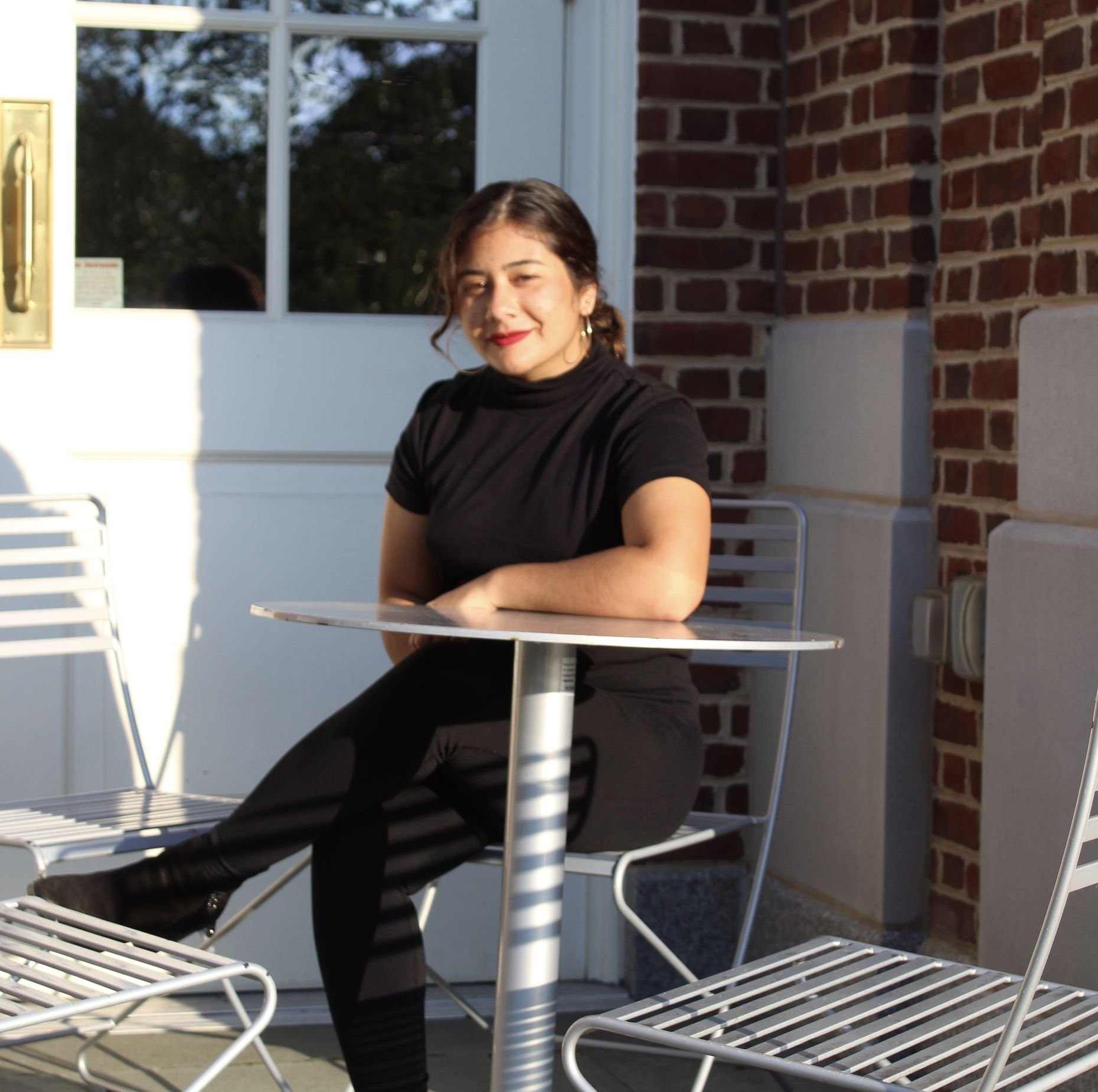 A photo of Marcy sitting at a table and smiling into the camera.