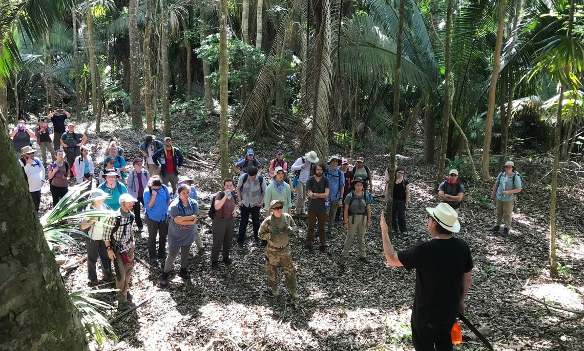 At the small site of Medicinal Trail in the jungle, students get a tour by Professor David Hyde of Western State Colorado University.  Medicinal Trail was a small village that stood in the area surrounding the larger settlement of La Milpa.
