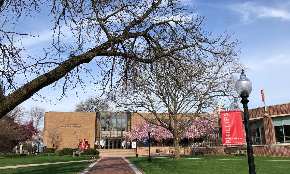 The front of the Steinman Syudent Center showing the Museum banners from Spring ,19 when trees are in bloom.