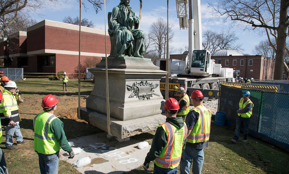 The crane carefully moves the statue to its new home, a few feet away. In the background is the Herman Arts Center, scheduled for demolition.
