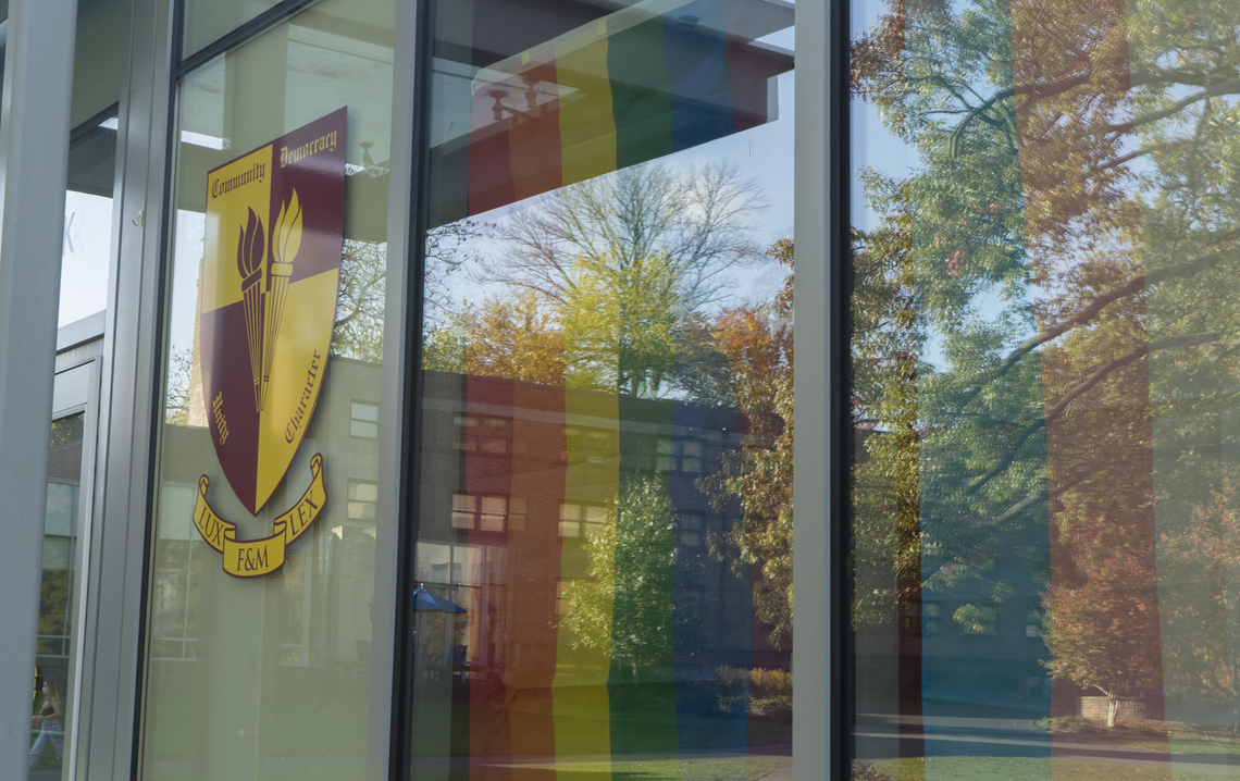 Light reflects from the front windows on the Bonchek College House Commons. The Bonchek logo and an LGBTQ pride flag are seen by the entrance.