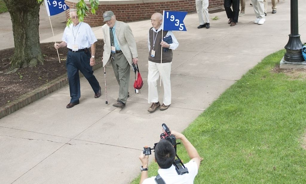 At 102, Eli Zebooker '35, the oldest alumni to attend Reunion Weekend, proudly carries his class flag in the Class Parade.