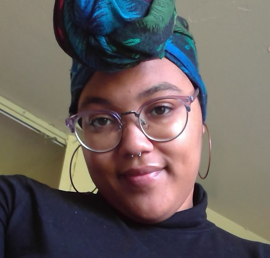 A photo of Ashley wearing a blue and green headwrap and smiling into the camera.