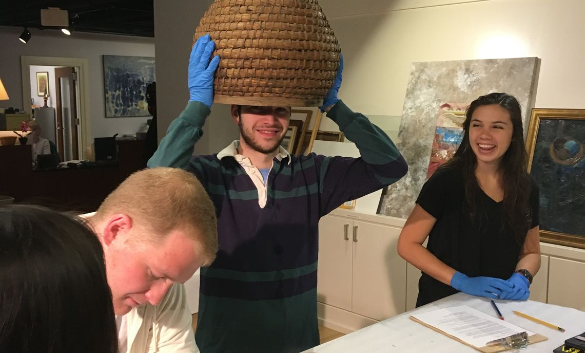 """Lior Wolf, center, a junior American Studies major, tries on an early beehive basket during a """"Culture Lab"""" at the Phillips Museum of Art as part of Prof. Alison Kibler's """"Studying American"""" course in Spring 2018. While junior AMS major Isabel Monge looks on, a third student examines another object."""