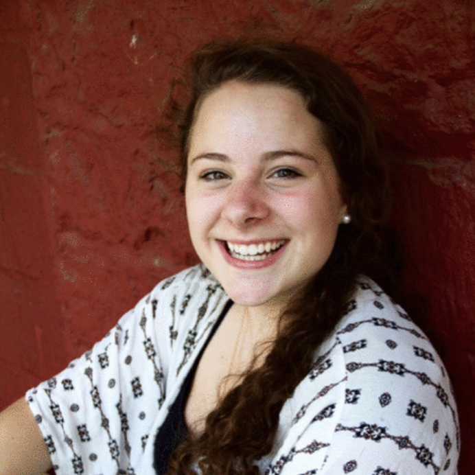 A photo of Ella in front of a red building smiling enthusiastically at the camera with her hair pulled over her shoulder.