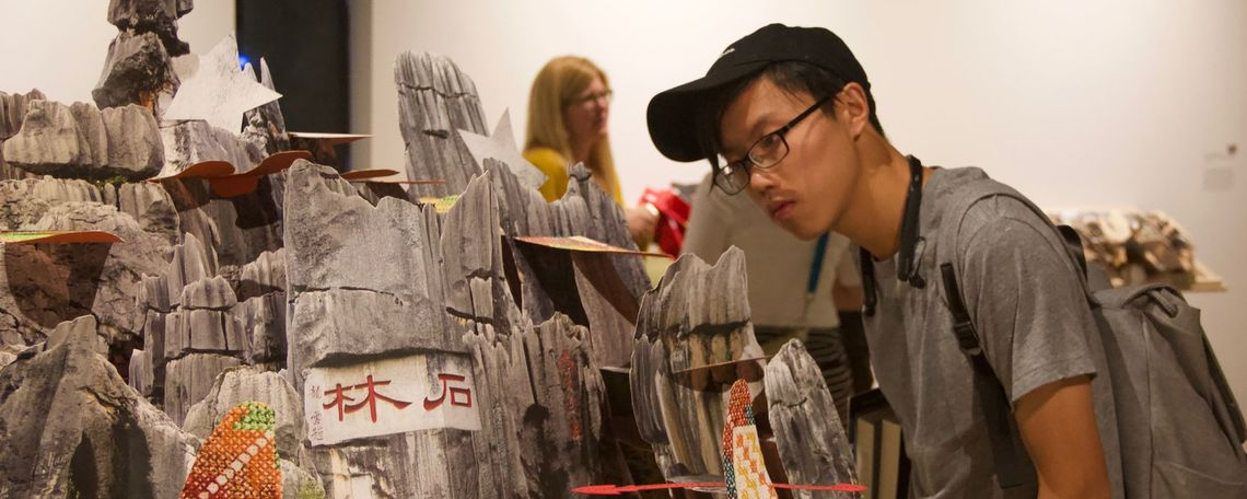 "A visitor looks at one of Colette Fu's pop-up books.  Colette Fu, ""Ashima,"" 2015, archival pigment ink pop-up book with embroidered Tyvek, Courtesy of Colette Fu"