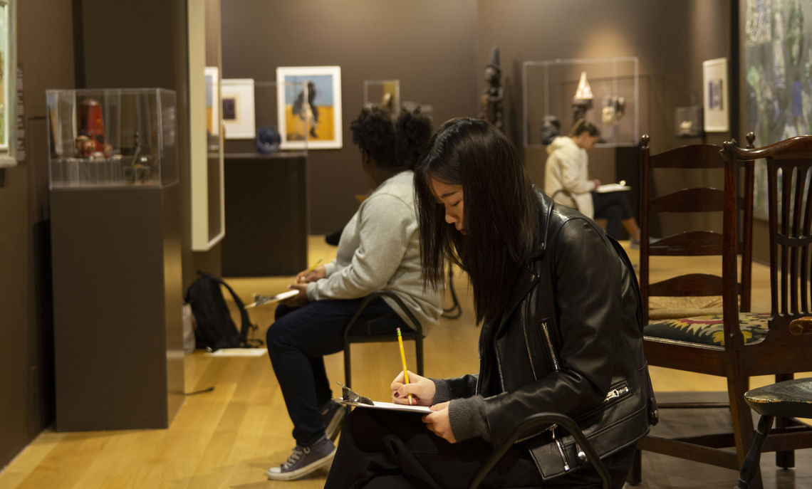 Students studying works in the Nissley Gallery as part of Professor Barlett's Psychology of Happiness class visit.
