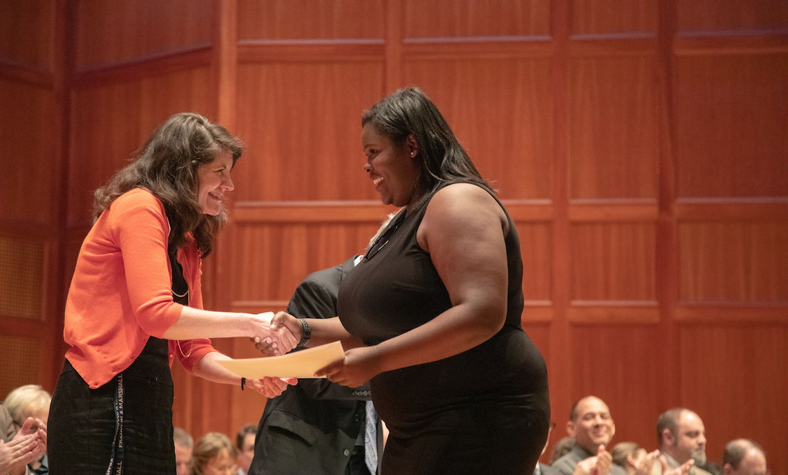 Sophomore Rachel St. Louis is presented with the Thomas Gilmore Apple Award by Dean of Students Colette Shaw. The Thomas Gilmore Apple Award also went to sophomore Rachel Strompf.