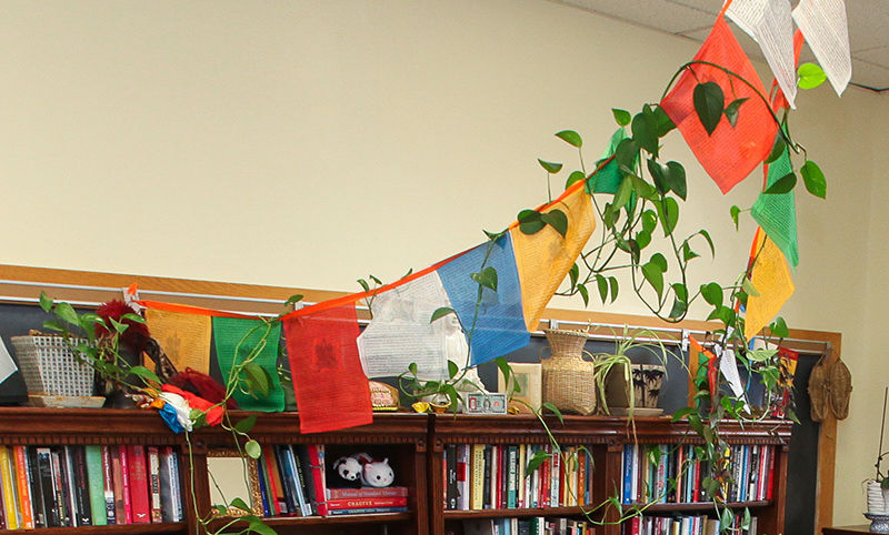 Colorful flags from Tibet hang prominently between the ceiling and bookcase.