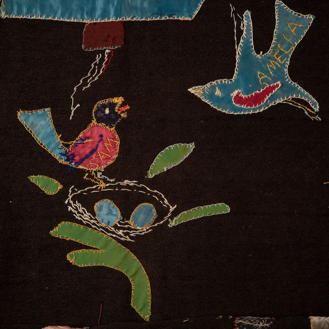 A child's bedcover, circa 1900, made of wool, silks, velvet, and knits. The maker is unknown. A gift from Robert Schaeffer.