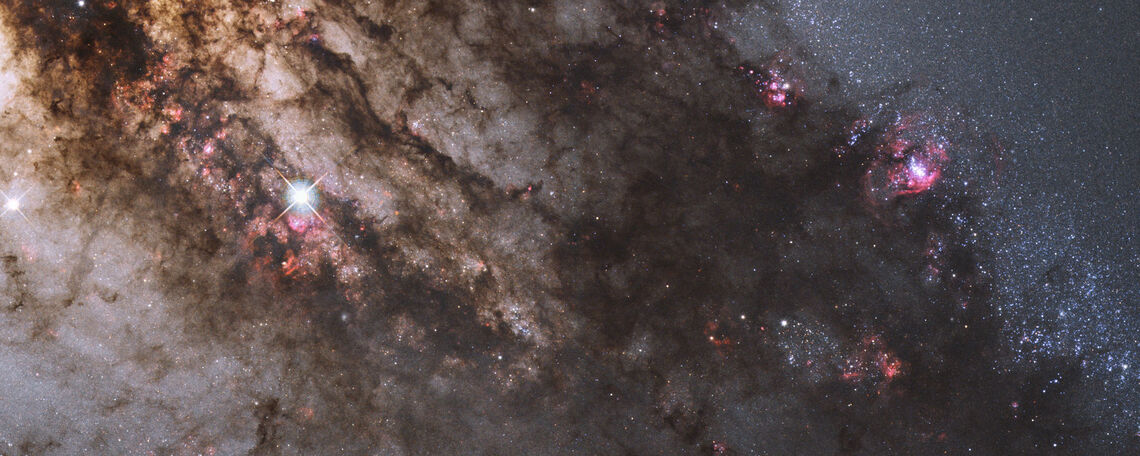Resembling looming rain clouds on a stormy day, dark lanes of dust crisscross the giant elliptical galaxy Centaurus A.