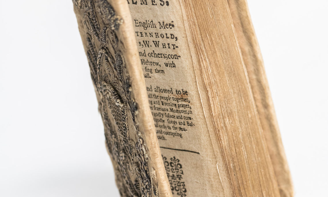 """""""The Whole Booke of Psalmes,"""" published in 1636, is an example of embroidered binding. It has contemporary satin cloth binding richly embroidered with silver wire in raised floral motifs."""