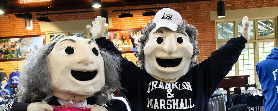 F&M mascots Ben Franklin and John Marshall pose in the campus bookstore located at the Distler House with F&M gear.