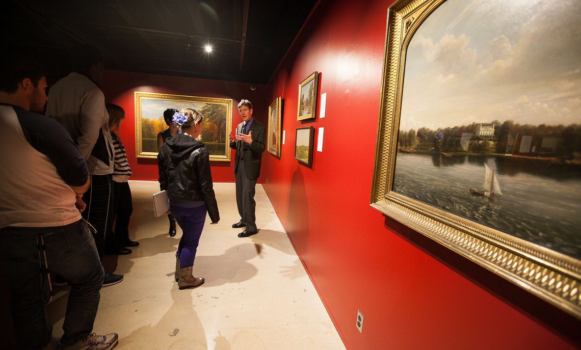 Art History Professor Michael Clapper teaches a seminar class in the Phillip's Museum of Art. They are pictured in the Hudson River exhibit.