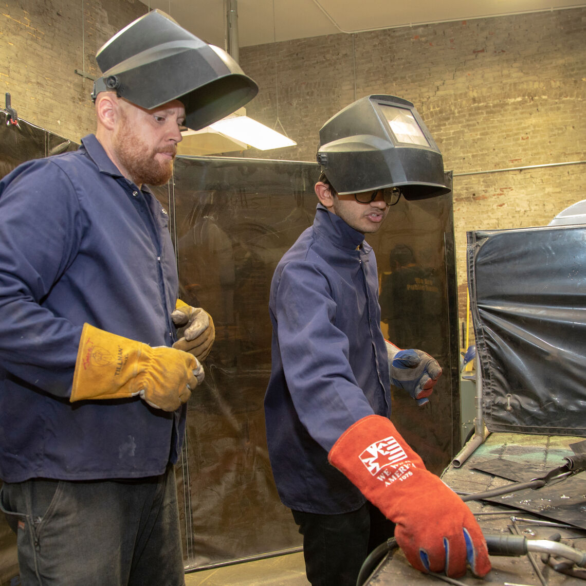 Jason Thompson, Winter Visual Arts Center Sculpture Studio Monitor, works with a student in welding class.