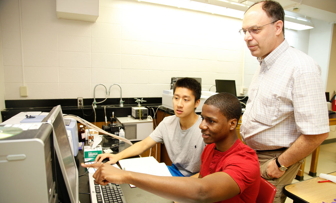 Hackman Scholars Marvin Nicoleau '16 (red shirt) and Hanyu (Peter) Sun '15 work on a summer research project in the chemistry department of the Hackman Science Building with Professor Rick Moog.