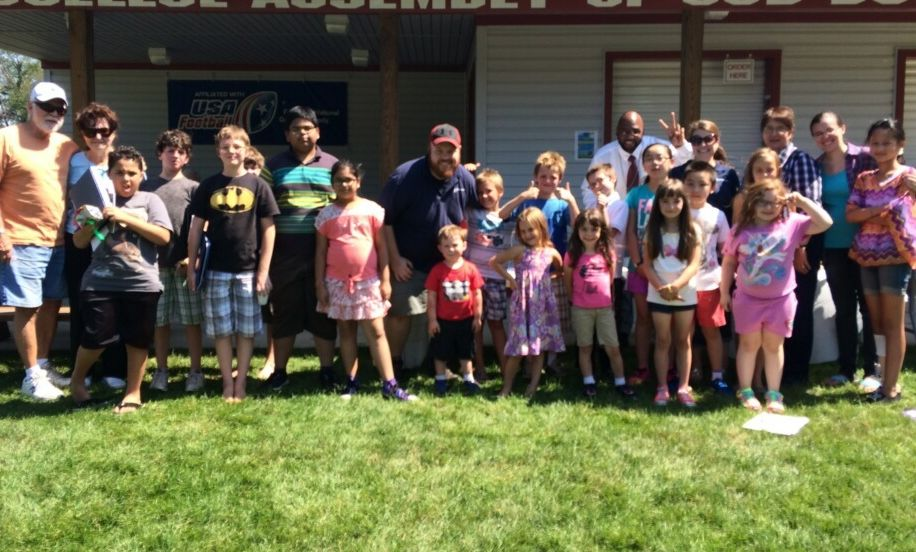 Chad Wright '11 (in center, with baseball cap), poses with some children and community members at a summer program held in conjunction with Big Brothers Big Sisters.