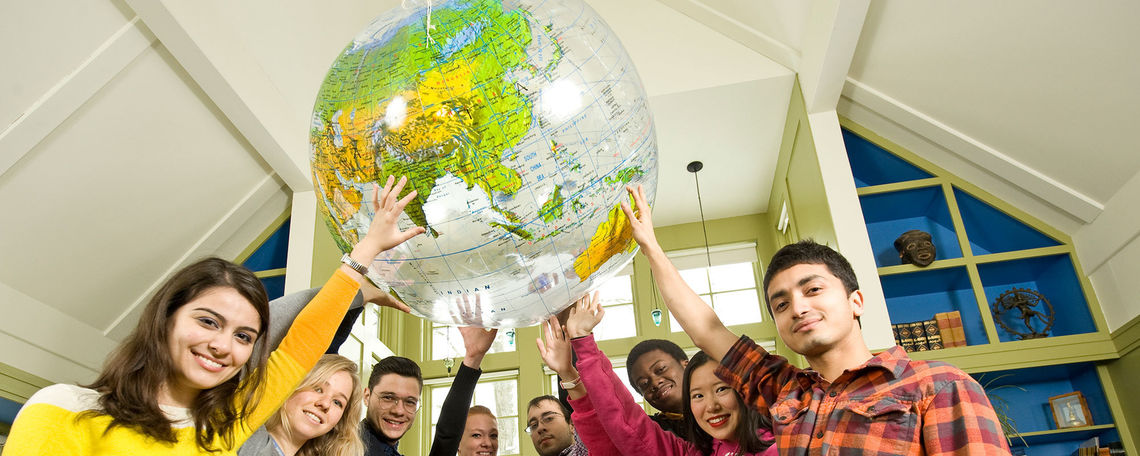 International students holding up a globe