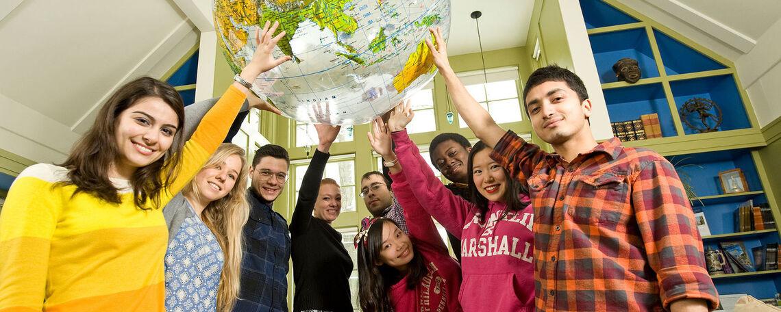 International students holding up a globe