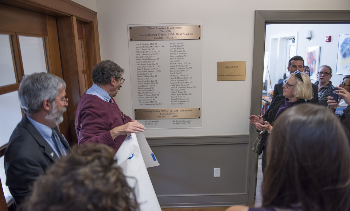 Visiting scholar David Stameshkin and Ralph Taber, associate dean of the College & director of the Klehr Center for Jewish Life, unveil a plaque listing the names of five decades of Hillel presidents as part of this year's celebration of Hillel's 50th anniversary.