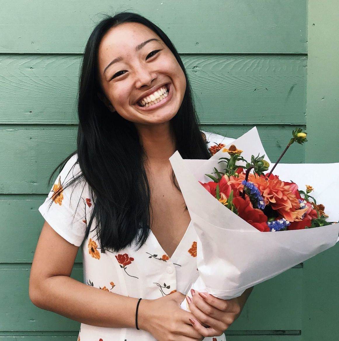 A photo of Leilani holding a bouquet of flowers in her hands in front of a green wall.