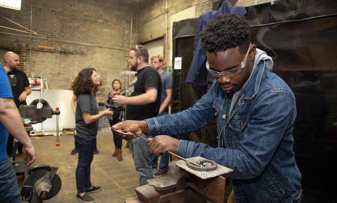 Senior environmental science major Boss Yolson Louis learns to twist metal.