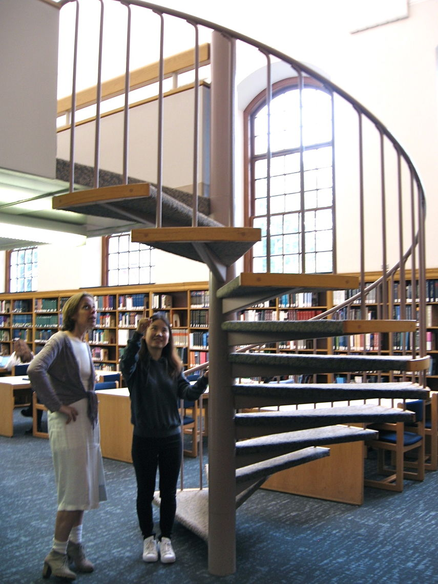 Prof. Annalisa Crannell and student researcher Yanlin Yang examine a spiral staircase leading to the second floor of Shadek-Fackenthal Library.