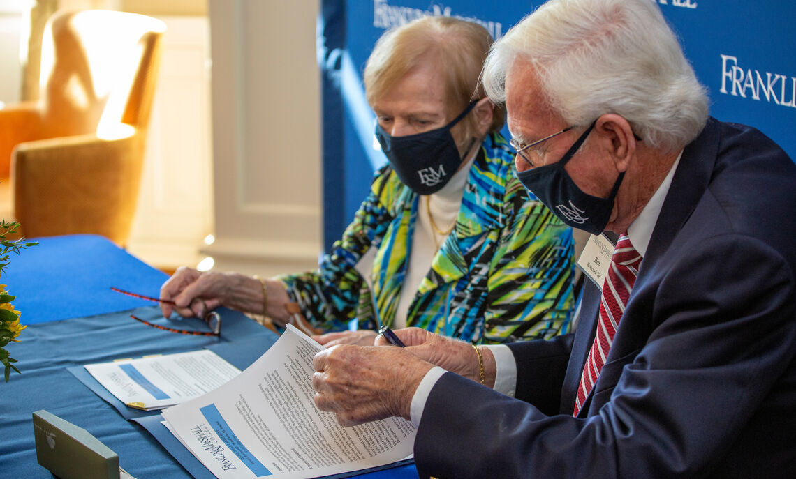 Dr. Robert '54 and Anna Roschel sign documents to make official their gift of $6.5 million to rename New College House as Roschel College House.