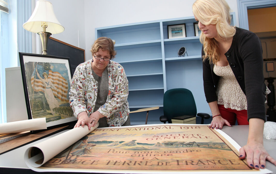 Anthropolgy professor Misty Bastian and Julie Kipperman '14 look at WWI era posters, photographs and postcards for a summer research project related to women labor during that period.