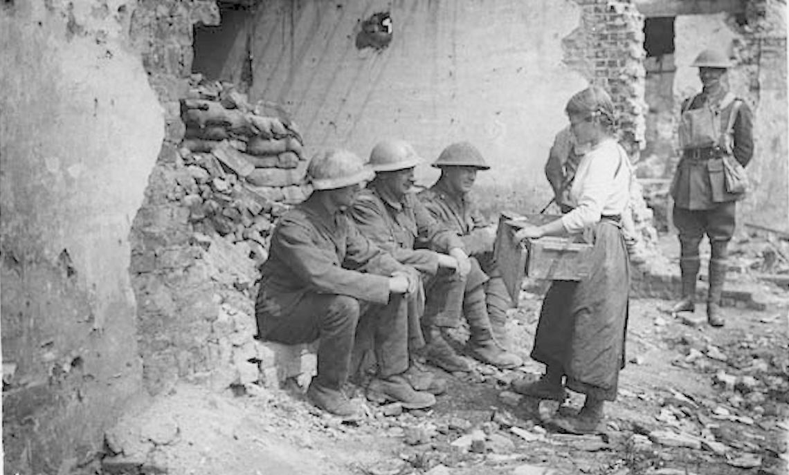 A young French girl attempts to sell what appear to be bars of chocolate to a small group of soldiers.