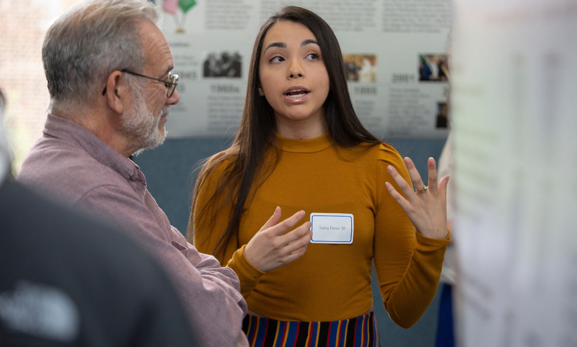 "At the Autumn Research Fair Friday afternoon, junior Taina Perez discusses one of her two projects: ""El Aguante of the Jiw and Nukak Tribes"" and ""Influences of Descriptive/Injunctive Norms, and Group Cues on Views of Freedom of Speech."" Associate Dean of the Faculty and Professor of Chemistry Marcus Thomsen, who opened the research fair, said, ""More than 100 students have participated in research over the last year."""