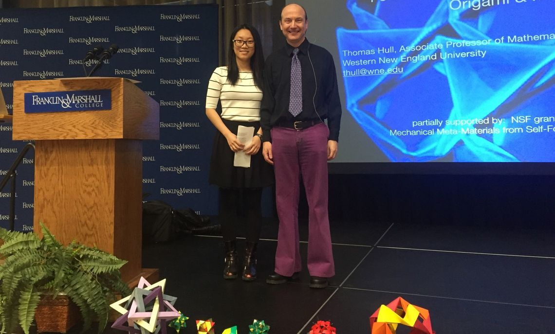 Math Club President Chengcheng Zhai '18 and Dr. Thomas Hull set up the stage for Common Hour, with several of Dr. Hull's origami models in the foreground.