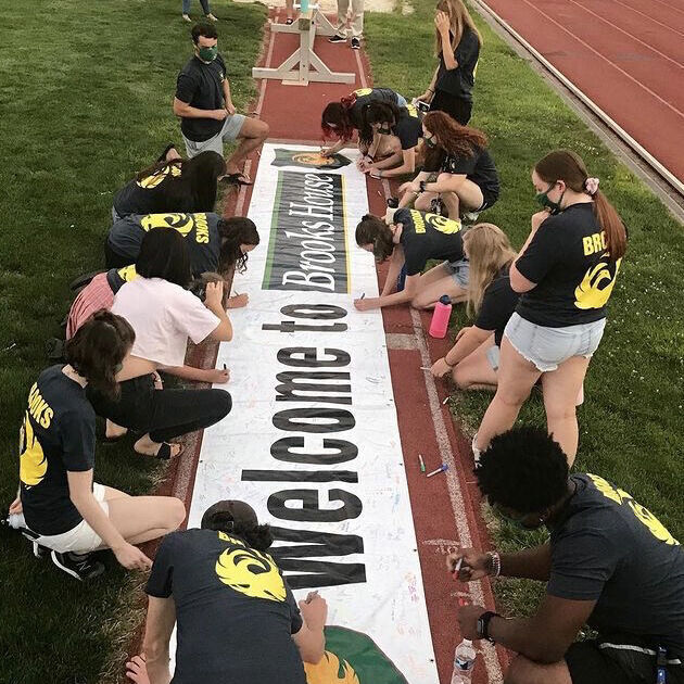 New members add their names to the banner at Orientation.