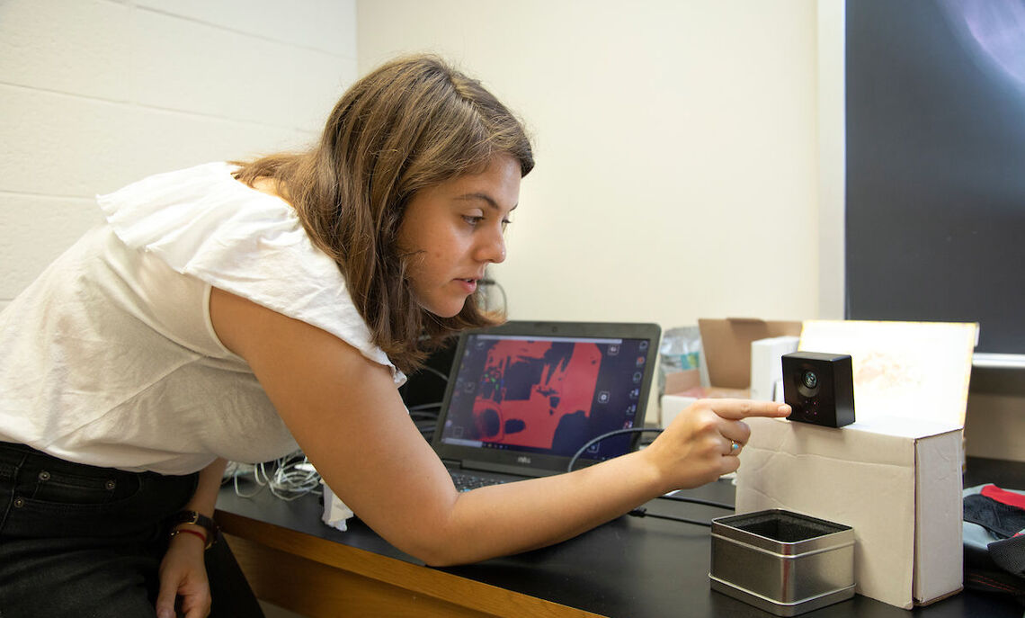 """Gaby Sallai's work as a summer Hackman Scholar involves testing a laser and a """"flight-of-time"""" camera for the four-wheeled robot."""