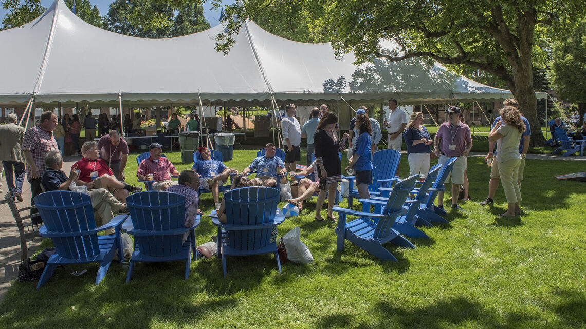 Alumni relax outside the big tent on Hartman Green, where inside a lunch of chicken, portabella mushrooms, greens and salads, and barbecue awaits while the Jazz Me Band offers musical accompaniment.