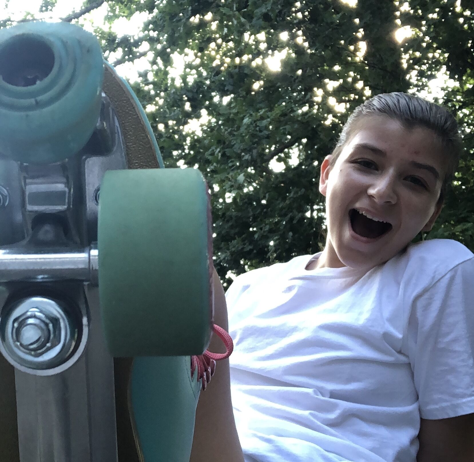 A photo of Gabby flipping a skateboard toward the camera and smiling.