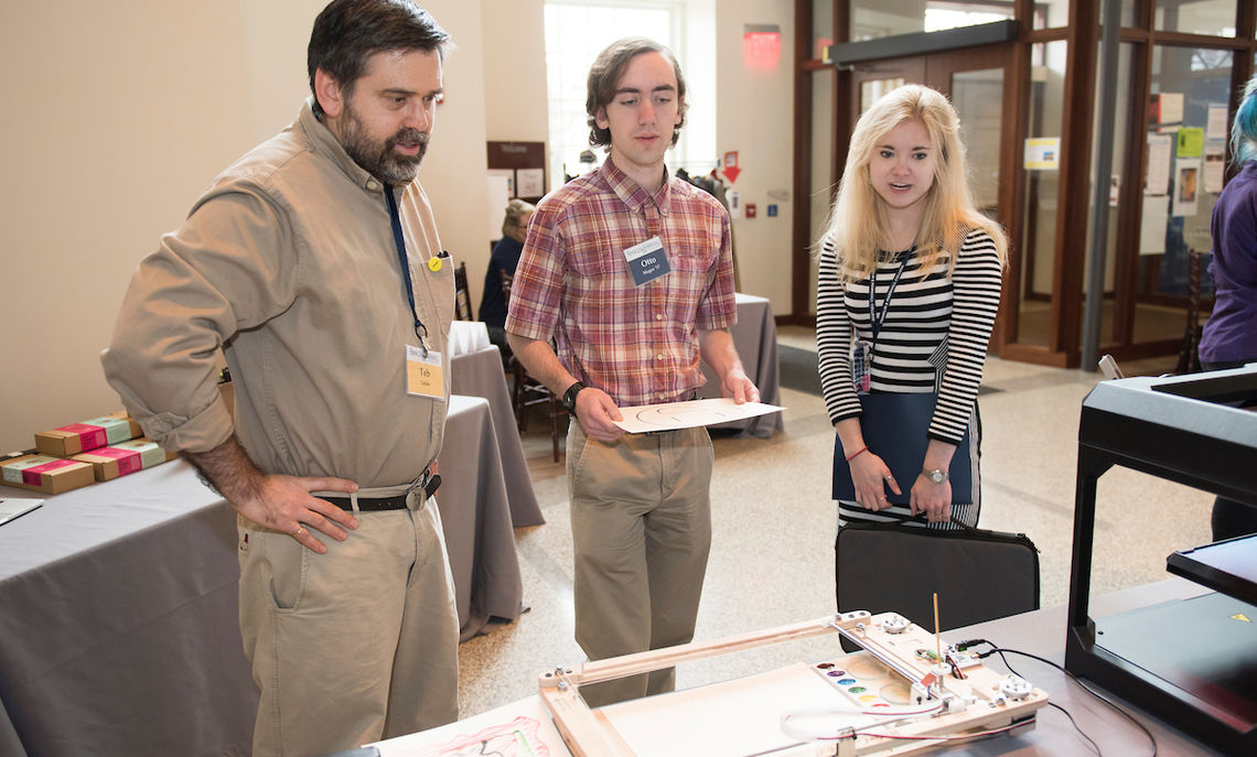 Teb Locke, F&M director of instructional and emerging technologies with juniors Otto Magee Jennifer Deasy examining a graphic machine, one of the innovations on display at the symposium.