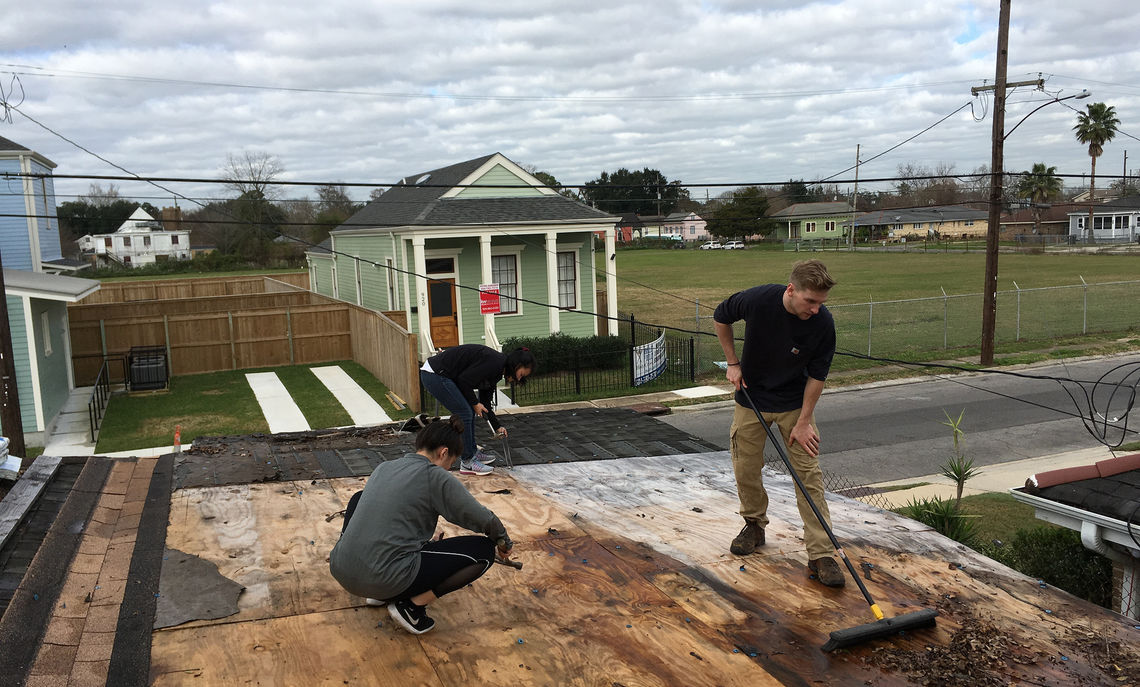 Seniors Soprina Guarneri, Katelin Dao and Luke Groff prepare an old roof for new shingles.