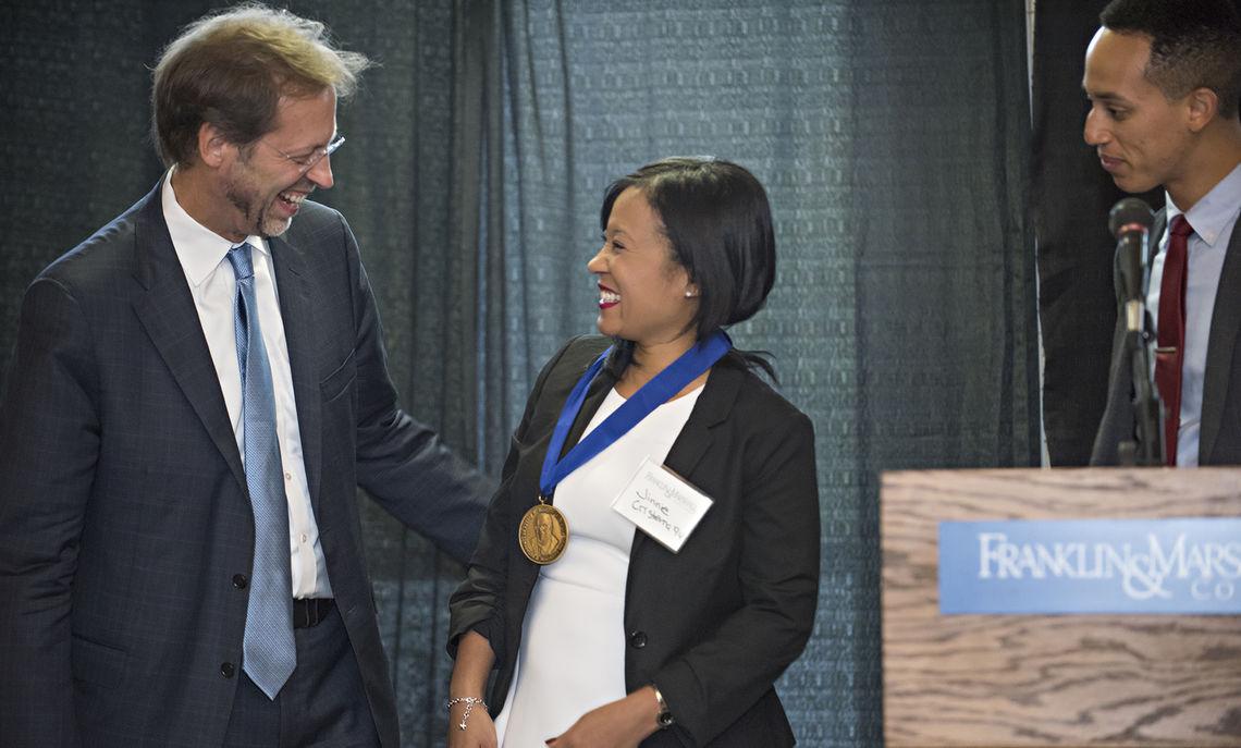 President Daniel R. Porterfield congratulates Bridgett Award recipient Jinnie Cristerna '94 during Saturday morning's African American Alumni Council Award Breakfast as Shadoe Tarver '10 looks on.