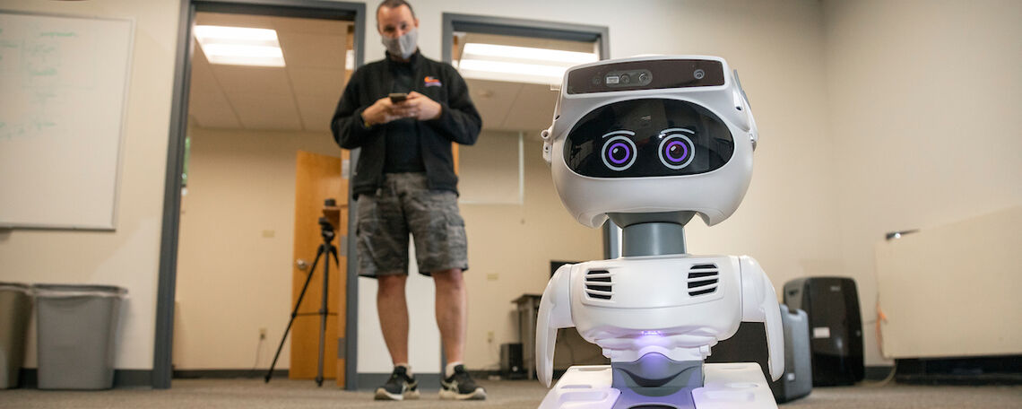Professor Willie Wilson in his computer science lab directing a social robot.