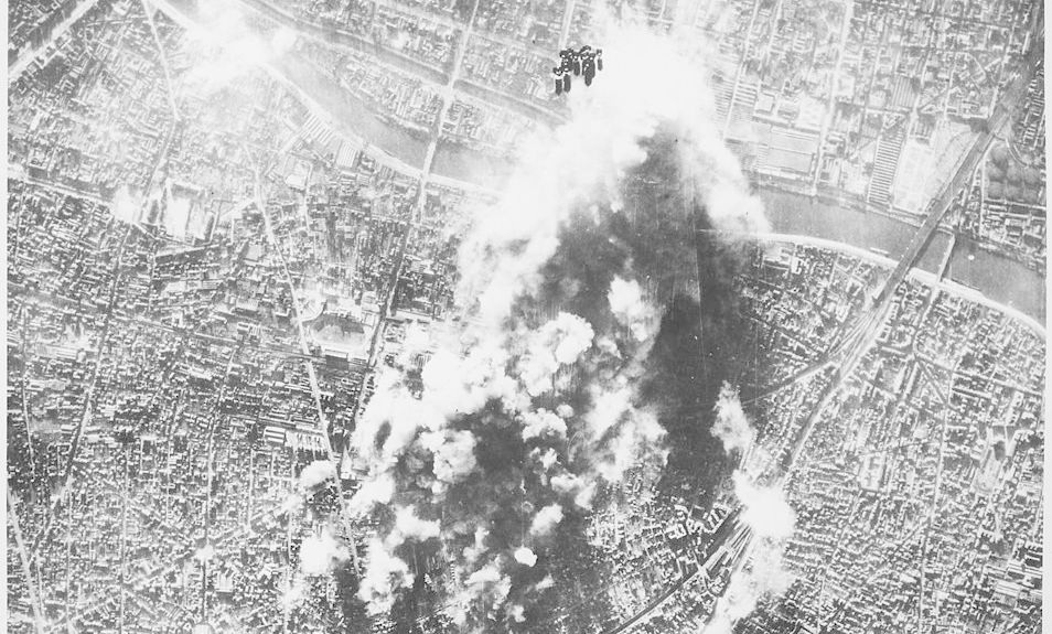 U.S. forces bomb an aircraft engine factory and a ball-bearing plant outside of Paris in December 1943. The photograph was taken from a B-17 Flying Fortress in the 8th Air Force Bomber Command and studied by Operations Research Services. Note the falling bombs at top center of photo.